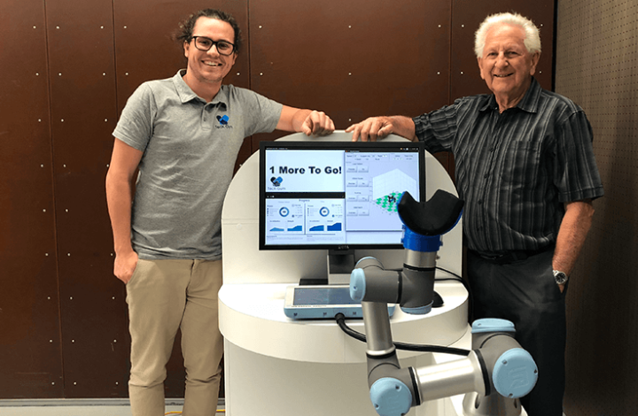 Photo of Tech Gym robotic arm with founder Rowan Smith.