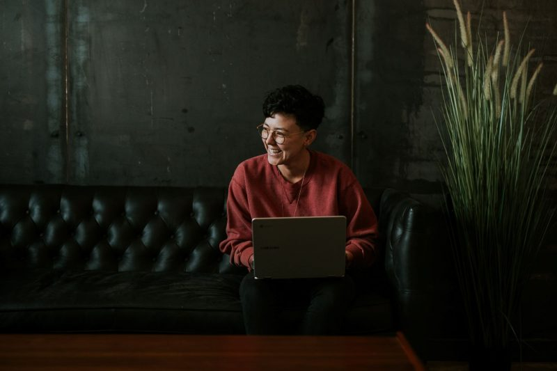 Photo of person laughing, sitting on couch with laptop.