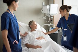Photo of two smiling nurses by bedside of smiling patient.