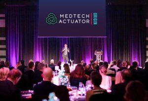 Photo of a pitch event with MedTech Actuator Origin logo in the stage background.
