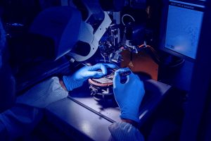 Photo of a person in a darkened lab in white coat and gloves making a medical device.