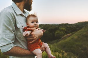 Photo of father and baby on a green hilltop at sunset.