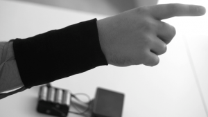 Black and white photo of a person wearing the CueSleeve around their wrist, pointing.