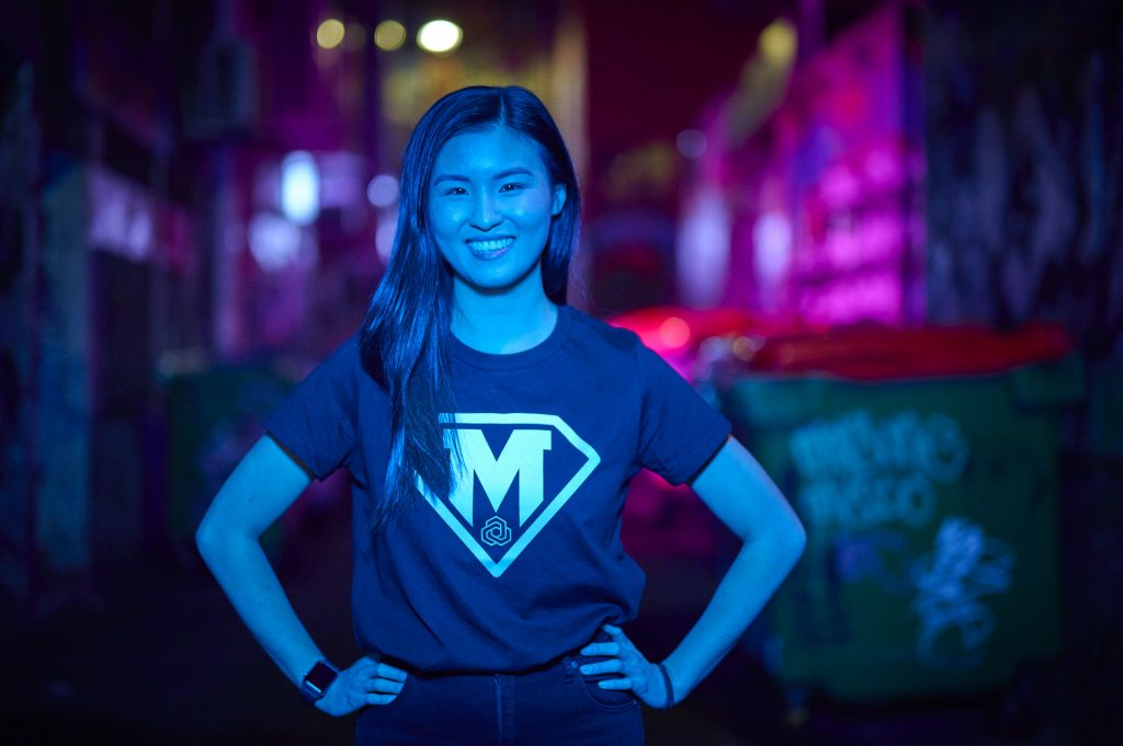 Photo of Amy Yu in MedTech Actuator superhero tee, Melbourne lane way by night.