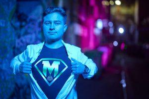 MedTech Actuator Origin alumnus and TuCann Co-Founder Santiago Beltran-Diaz, in MedTech Actuator superhero tee in Melbourne laneway by night.